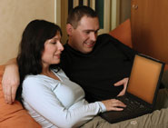 Couple on sofa using wireless laptop computer