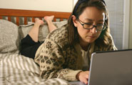 Mature woman with wireless laptop accessing web from bed