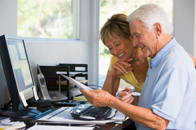 Senior couple using wireless IT equipment in home office